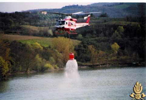 Foto che ritrae un'elicottero antincendio dei Vigili del fuoco che sta riempendo la sua cisterna d'acqua in un lago